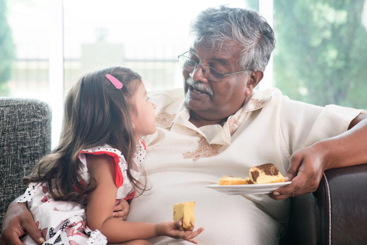Grandpa and granddaughter eating cake